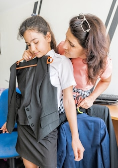 A schoolgirl tries on a vest