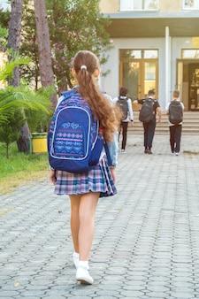Schoolgirl in uniform goes to school, education.