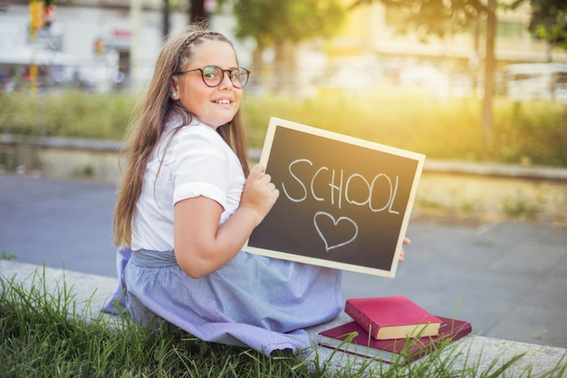 Schoolgirl in uniform with sign school love