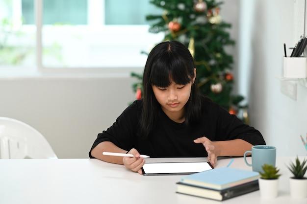Школьница с помощью цифрового планшета изучает свой онлайн-урок дома. концепция онлайн-образования.