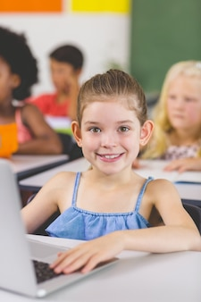 女子高生は教室でラップトップを使用して