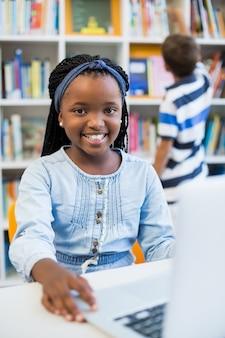 Schoolgirl using laptop in library