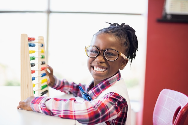 Schoolgirl using a maths abacus at school