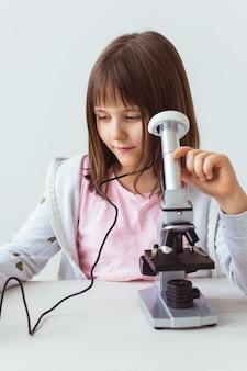 科学の授業で顕微鏡を使用しての女子高生。テクノロジー、レッスン、子供のコンセプト。