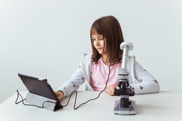 Schoolgirl using microscope in science class. technologies, lessons and children concept.