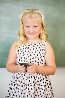 Schoolgirl using mobile phone in classroom