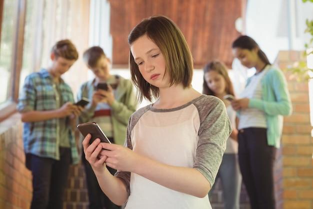 廊下で携帯電話を使用しての女子高生