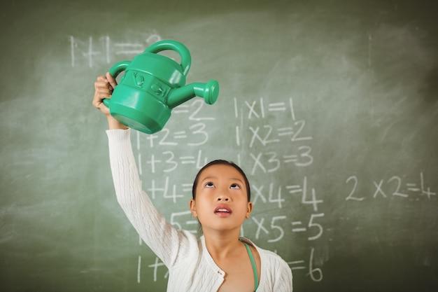 Schoolgirl using a watering can