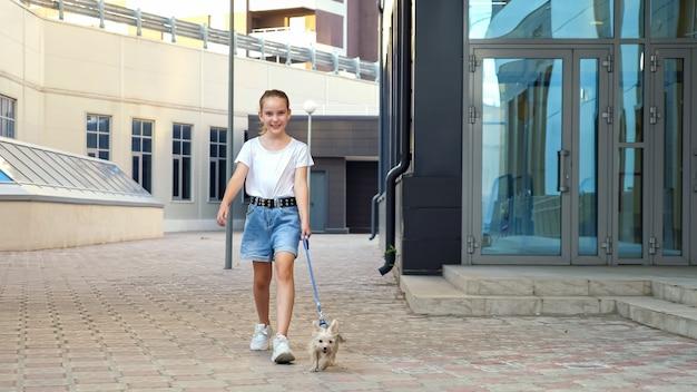 여 학생은 거리를 따라 개를 산책합니다. 가죽 끈에 강아지와 함께 흰색 티셔츠와 파란색 데님 반바지에 십 대 소녀는 도시 건물 과거 포장에 간다