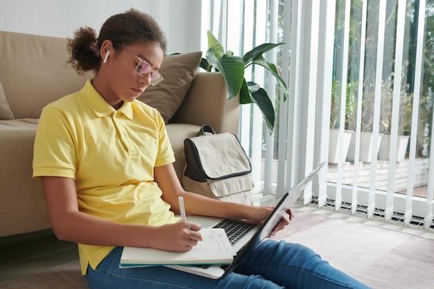 Школьница смотрит лекцию на ноутбуке