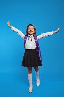 Школьница в униформе и рюкзаке поднимает руки к синей стене