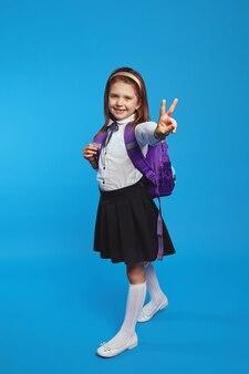 Школьница в униформе и рюкзаке улыбается и показывает жест мира