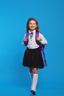 Школьница в униформе и рюкзаке улыбается и гуляет на синем фоне