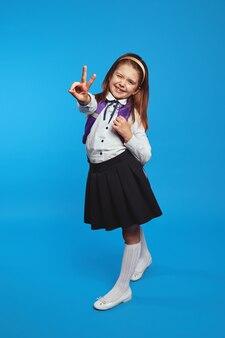 Школьница в униформе и рюкзаке улыбается, показывая жест мира