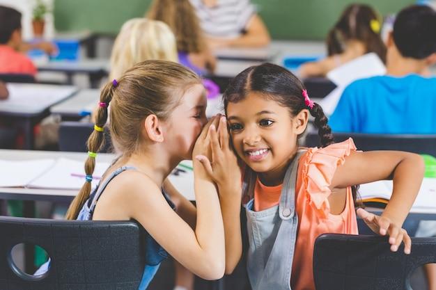 Schoolgirl whispering into her friend s ear in classroom