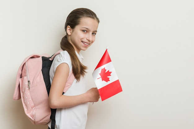 Schoolgirl in white t-shirt with a backpack holding the flag of canada