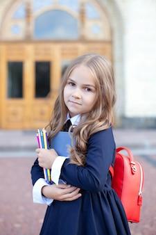 Школьница с книгой, карандашом и школьной сумкой.
