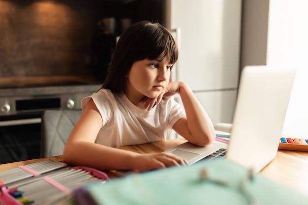 ノートパソコンを持つ女子高生は家で宿題をします。オンライン学習。ビデオ通話で女の子の研究。検疫中の遠隔教育
