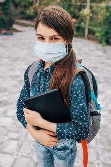 Школьница с медицинской маской на лице и ноутбуком в руке