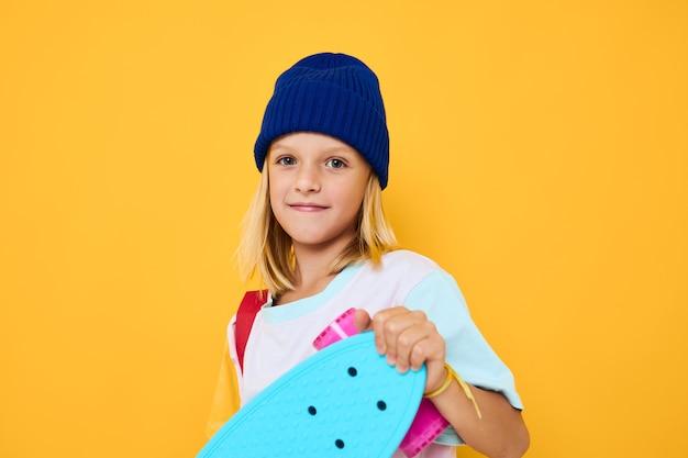彼の頭の子供のライフスタイルの概念にスケートボードを持つ女子高生