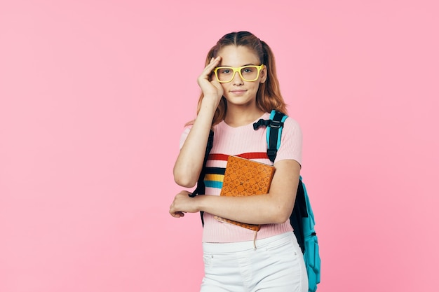 Schoolgirl with backpack books in hand learning education pink background
