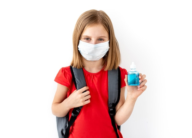 白で隔離される手で消毒剤を保持している医療マスクのバックパックと女子高生
