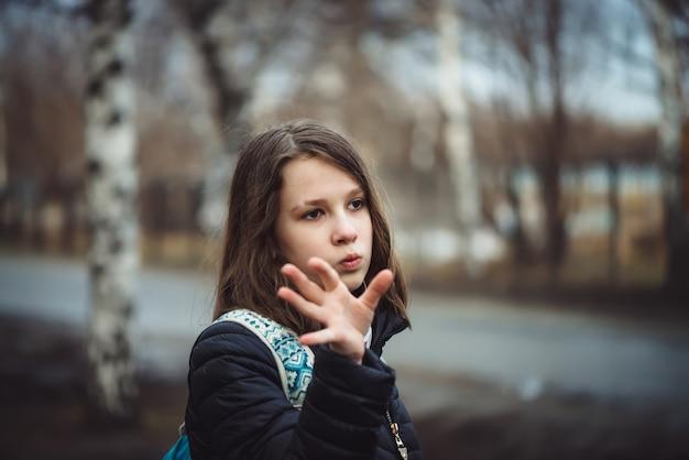 バックパックを持つ女子高生は、雨の曇りの日に街に沿って落ち込んだ状態で歩きます。色あせたトーンで濡れた髪の少女はコピースペースで屋外です。
