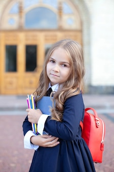 Schoolgirl with a book, pencil and school bag.
