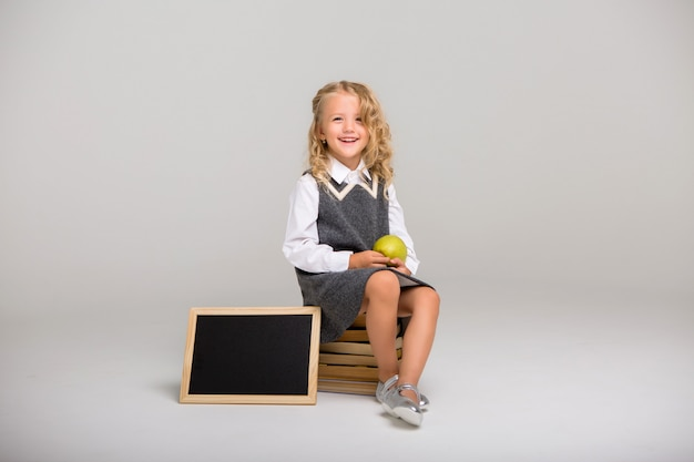 Schoolgirl with books on a light background