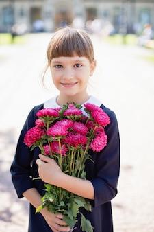 Schoolgirl with bouquet in school uniform