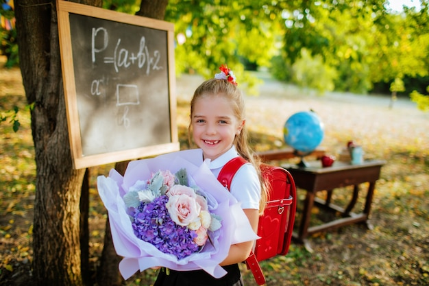 Schoolgirl with a briefcase and a bouquet of flowers