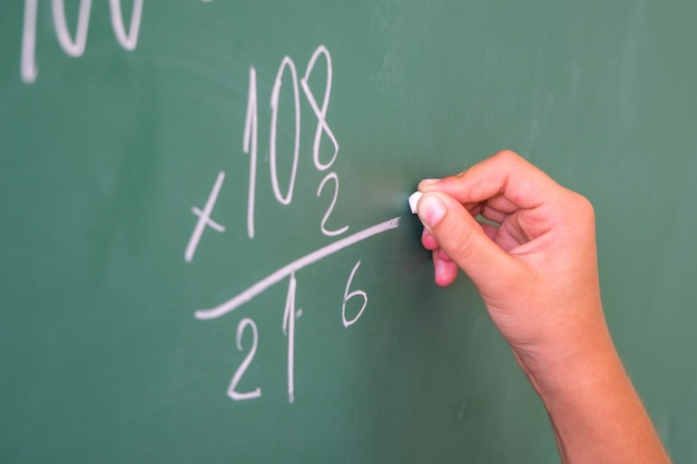 Schoolgirl with chalk at the blackboard solves a math problem.
