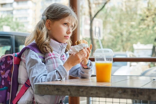 Schoolgirl with cheeseburger and orange juice, fast food restaurant background