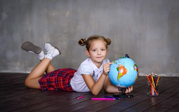 Schoolgirl with colors and globe earth. school concept