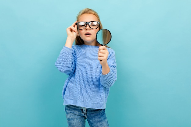 Schoolgirl with glasses and a magnifier on a blue background
