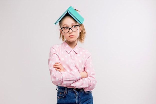 Schoolgirl with glasses with a book on the head