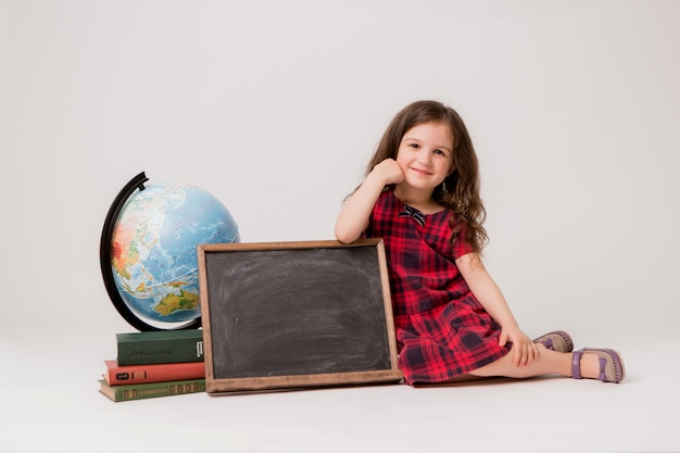 Schoolgirl with globe, books and blank drawing board on white background