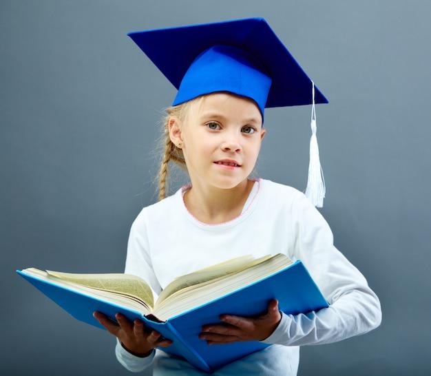 Schoolgirl with graduation cap holding a heavy book