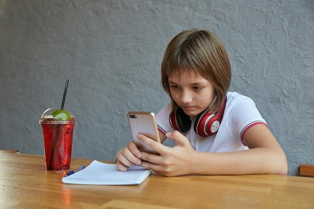 Школьница с наушниками и красным ледяным лимонадом использует смартфон для серфинга в интернете