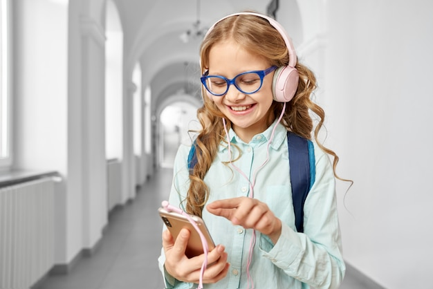 Schoolgirl with holding call phone and listening music