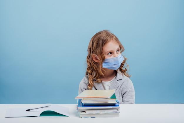 얼굴에 의료 마스크를 쓴 여학생은 탁자 파란색 배경에 책을 가지고 있다