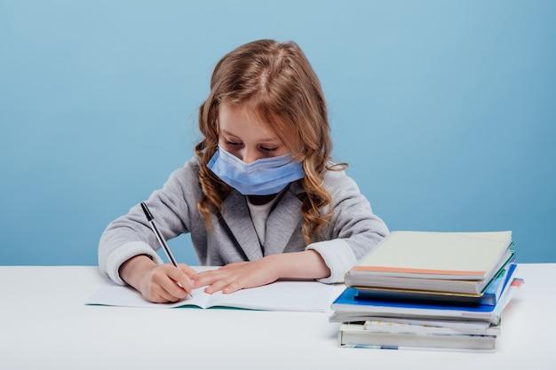 의료 마스크를 쓴 여학생은 파란색 배경에 격리된 테이블에 앉아 공책에 씁니다.