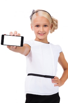 Schoolgirl with mobile phone in hand looking at the camera
