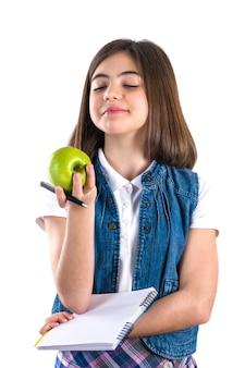 Schoolgirl with notebook and apple on white background.