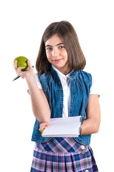 Schoolgirl with notebook and apple on white