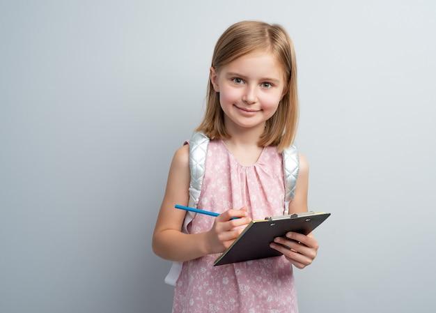 屋内の手書きパッドでメモを取る鉛筆を持つ女子高生