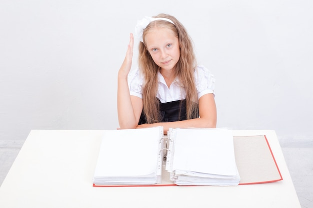 Schoolgirl  with red folders sitting at the table over white background