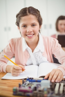 教室で電子プロジェクトに取り組んでいる女子高生