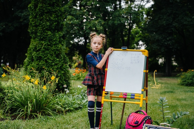 A schoolgirl writes lessons on a blackboard and is engaged in outdoor training