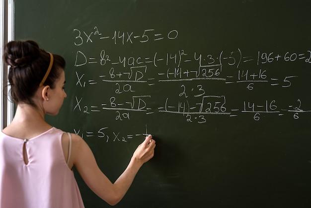 黒板にチョークで高校の数学の数式を書く女子高生、数学のクラスの代数